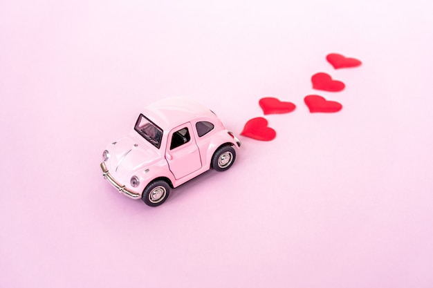 Pink retro toy red car on pink background with heart confetti.