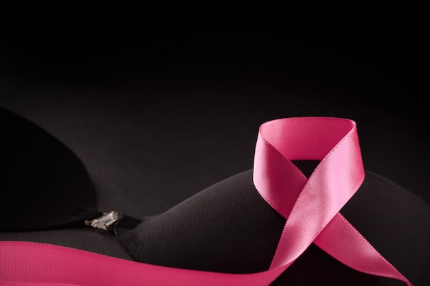 Pink ribbon on a black bra to support a breast mammary cancer awareness campaign in october.