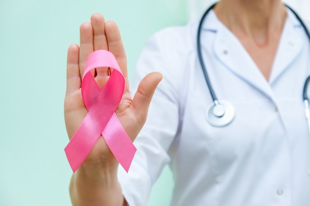 Pink ribbon for breast cancer awareness in doctor's hand, women breast tumor illness campaign.
