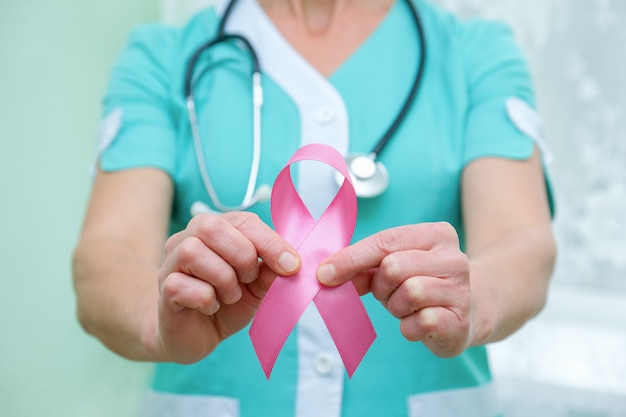Pink ribbon for breast cancer awareness in doctor's hands, women breast tumor illness campaign.