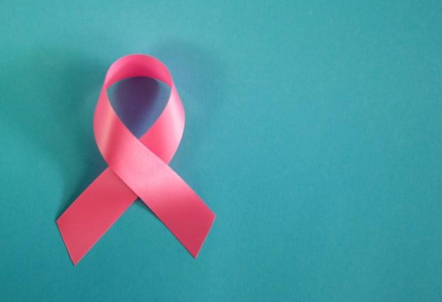 Розовая лента для осведомленности о раке груди на бирюзовой поверхности