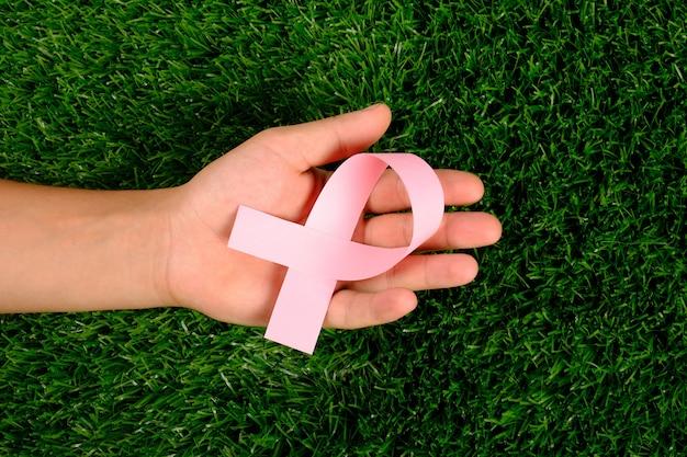 緑の芝生でがんとの闘いのシンボルを手にピンクのリボン。