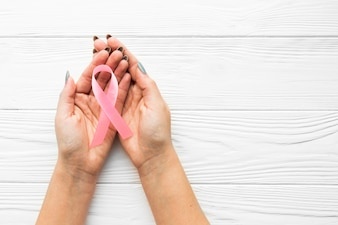 Pink ribbon on hands over lumber background