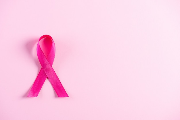 Pink ribbon on pink paper background for supporting breast cancer awareness
