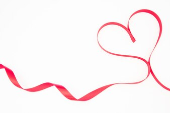 Pink ribbon shaped into heart with copy space