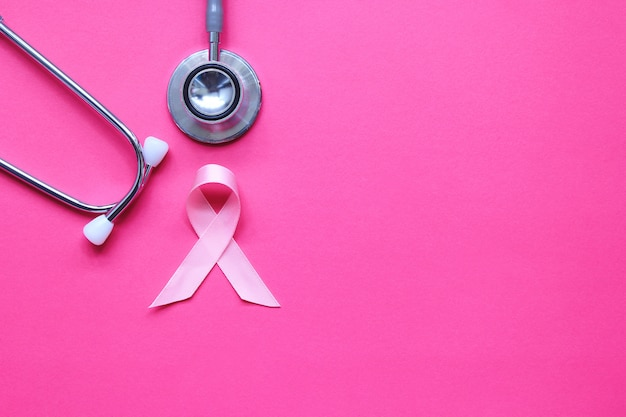 Pink ribbon and stethoscope on pink background with copyspace, symbol of breast cancer in women, health care concept