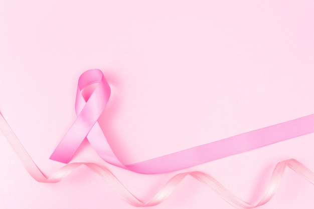 Pink ribbon symbol for breast cancer awareness concept over pink background with copy spac