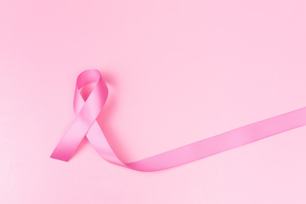 Pink ribbon symbol for breast cancer awareness concept over pink background