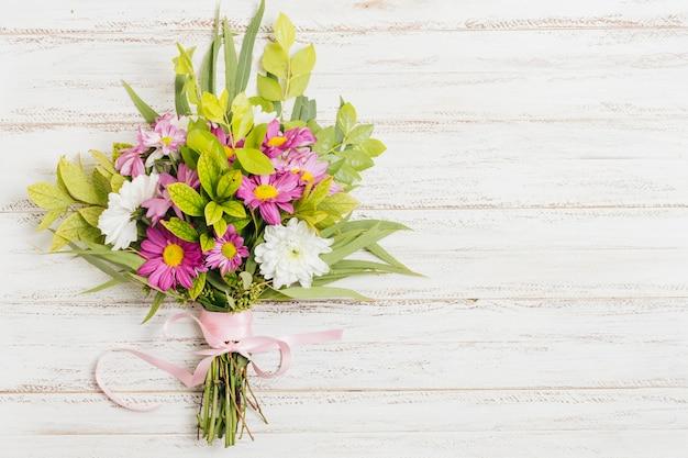 木製の机の上の花の花束と結ばれるピンクのリボン