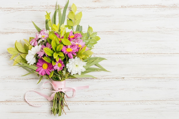 Pink ribbon tied with flower bouquet on wooden desk