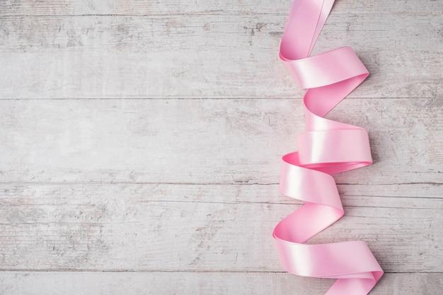 Pink ribbon on white wood.