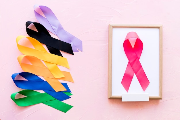 Pink ribbon on white wooden frame near the row of colorful awareness ribbon