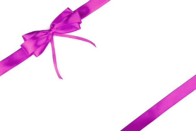 白い表面に分離された弓とピンクのリボン