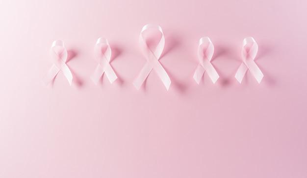パステルカラーの背景にピンクのリボン女性の乳がんの意識のシンボル