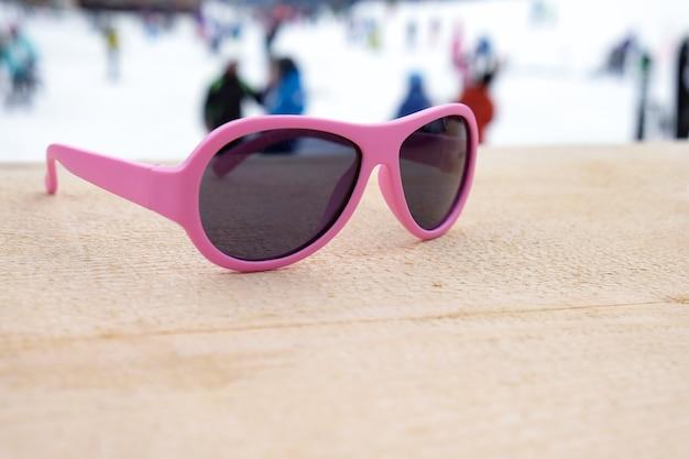 Apresスキーバーまたはカフェの木製の斜面にピンクの縁取りのサングラス、背景にスキー斜面、コピースペース。ウィンタースポーツ、レジャー、レクリエーション、リラクゼーションの概念