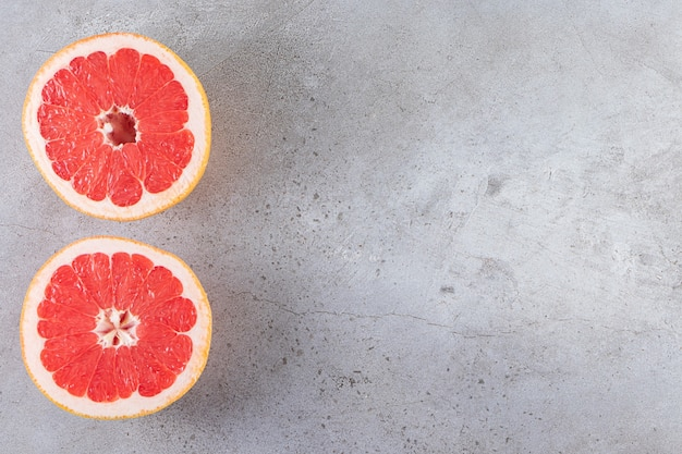 Pink ripe grapefruit slices placed on a stone table.