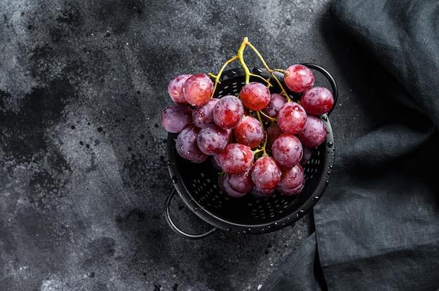 ザルにピンクの熟したブドウ