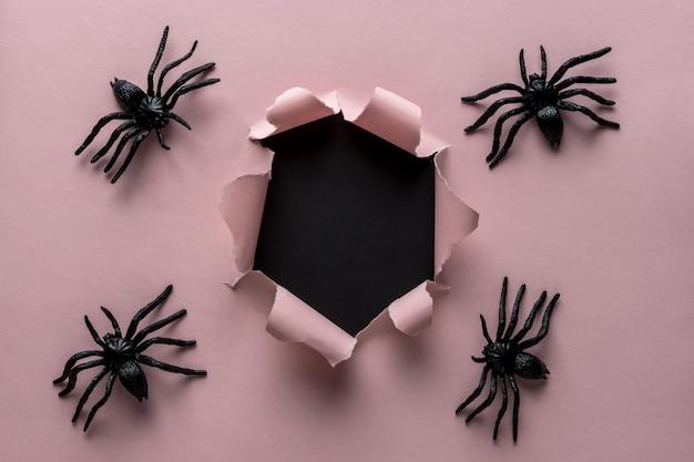 Розовая рваная бумага с фоном пауков