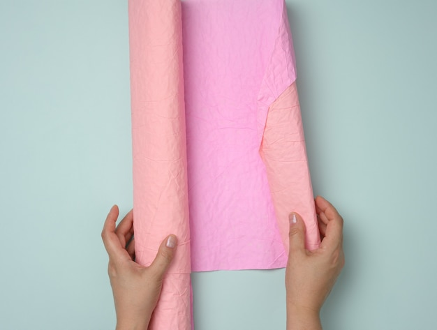 Pink roll of wrapping paper in female hands on a blue background, top view