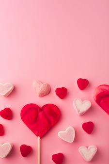 ハート型の甘いお菓子とピンクのロマンチックな休日の背景。テキスト用のスペースを持つ聖バレンタインの装飾的なカード。愛のテーマ。