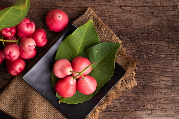 Pink rose apple on wood table.