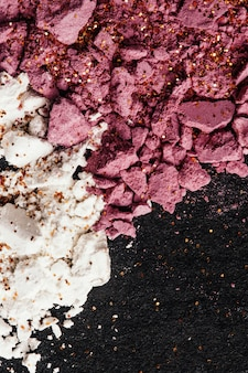 Pink rose blush and white face powder lie broken on the table