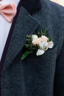 Pink rose boutonniere flower on groom's wedding coat