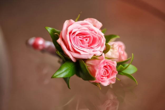 Pink rose boutonniere for groom
