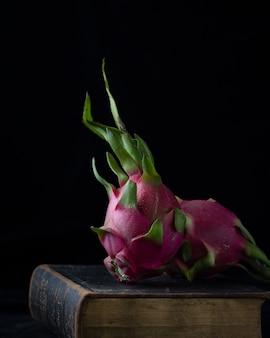 古い本の上のピンクのバラのつぼみ