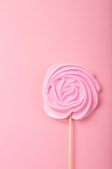 Pink  rose candy in pastel colors on a wooden stick on a grey  background, valentine, mother's day.