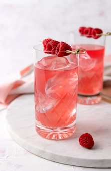 Pink rose cocktails with raspberry in crystal glass on table