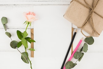Pink rose; colored pencil and wrapped gift box on wooden table