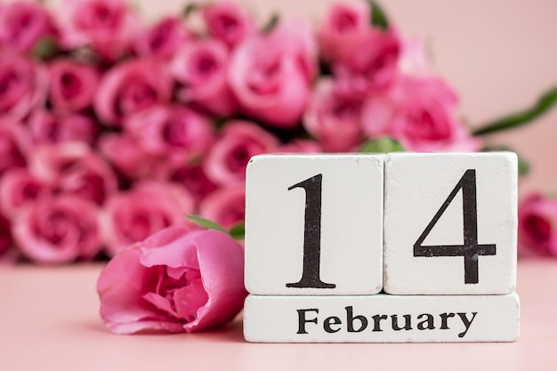 Pink rose flower and 14th february calendar on pink background. love, romantic and happy valentines day holiday concept