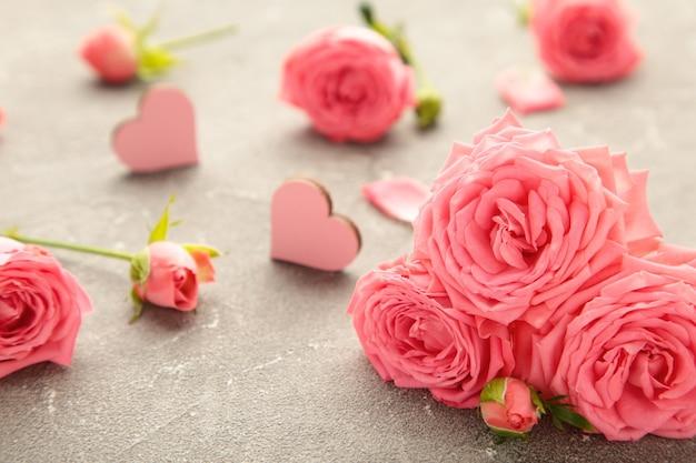 Розовый цветок розы с сердечками на сером фоне. концепция весны. вид сверху