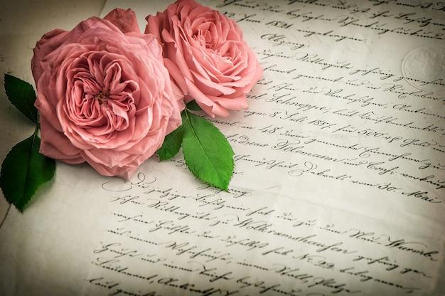 ピンクのバラの花と古い手書きの手紙。ヴィンテージ紙の背景。ビネット付きのレトロなスタイルのトーンの写真。セレクティブフォーカス