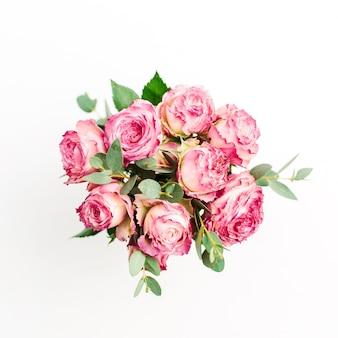 白地にピンクのバラの花の花束。フラットレイ、トップビュー