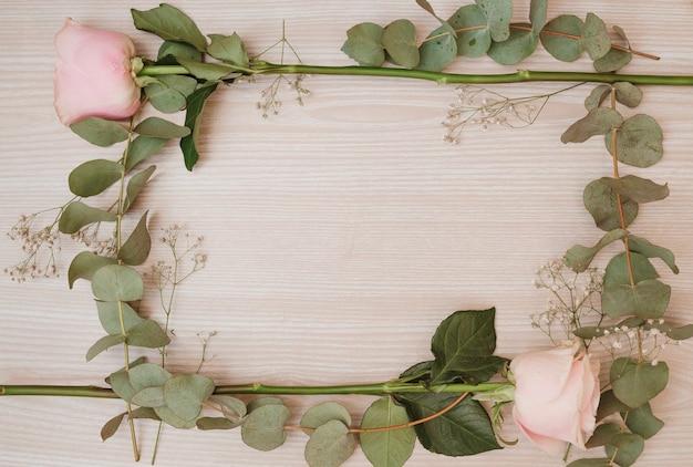 Pink rose flowers frame on wooden desk