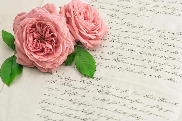 アンティークの手書きの手紙の上にピンクのバラの花。ヴィンテージ紙の背景。セレクティブフォーカス