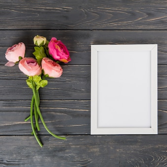 Pink rose flowers with blank frame on wooden table