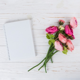 Pink rose flowers with blank notebook on table