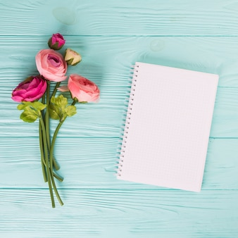 Pink rose flowers with blank notebook on wooden table