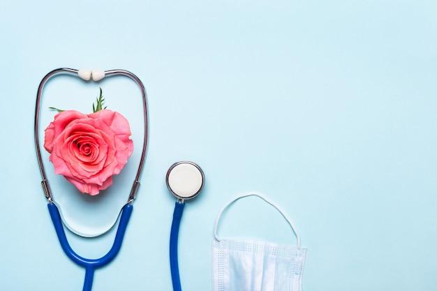 Розовое сердце розы, стетоскоп и защитная маска на синем фоне. спасибо, доктор и концепция дня медсестры.