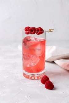 Pink rose iced cocktail with raspberry in crystal glass on table