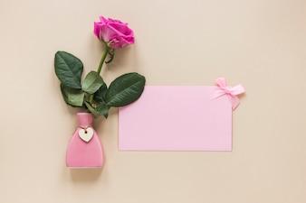 Розовая роза в маленькой вазе с бумагой на столе