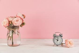 ピンクの背景に木製の机の上のガラスの瓶と灰色のヴィンテージの小さな目覚まし時計でピンクのバラ