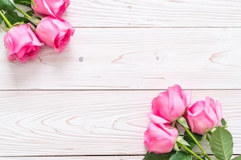 Pink rose in vase on wood background
