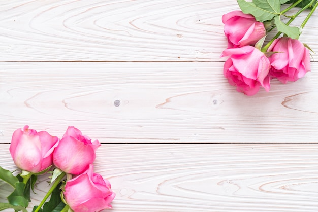 Розовая роза в вазе на фоне дерева