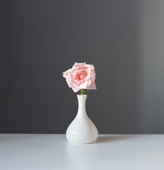 회색 배경에 흰색 꽃병에 핑크 장미