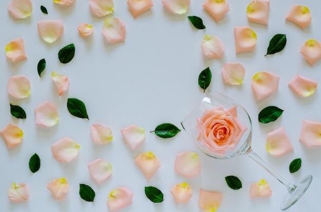 サンバレンタインの日に白い背景とハート形のスペースに花びらと葉でワイングラスにピンクのバラ