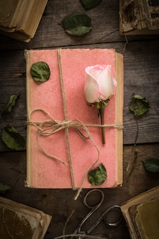 Pink rose on an old book in a vintage style.
